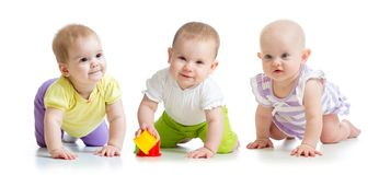 Cute smiling babies weared clothes crawling isolated on white. Cute smiling babies girls weared clothes crawling isolated on white royalty free stock image