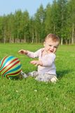 Cute smiling baby with ball sits on green grass Royalty Free Stock Image