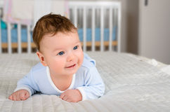 Cute smiling baby boy in bed lying on his belly Royalty Free Stock Photos