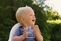 Cute smiling baby boy with a glass of water sitting in a baby chair against green bush Stock Photos