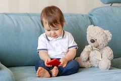 Cute smiling baby boy playing on smartphone sitting on sofa with teddy bear at home royalty free stock photos