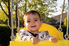 Cute smiling baby in bucket swing. At the park royalty free stock photo