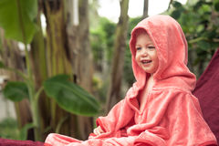 Cute smiling baby covered with soft pink blanket sitting on sunbed outdoors on green tropical background with palm trees and copy Stock Photos