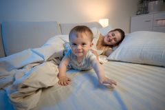 Cute smiling baby boy crawling on bed towards camera. Cute smiling baby crawling on bed towards camera Royalty Free Stock Images