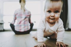 Cute Smiling Baby Crawls and Mother Sitting Back stock photos