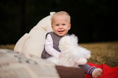 Cute smiling baby girl sitting on a blanket in the park. Cute smiling baby girl dressed in a warm dress sitting on a blanket in the autumn park Stock Photos