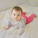 Cute smiling baby girl lying in the bed Royalty Free Stock Images
