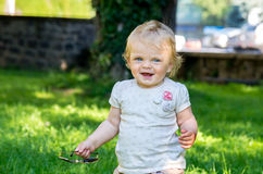 Cute smiling baby girl on the street in the summer. Stock Photography