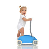 Cute smiling baby girl toddler with toy walker make first steps. Isolated on a white background Royalty Free Stock Photography