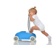 Cute smiling baby girl toddler with toy walker make first steps Royalty Free Stock Image