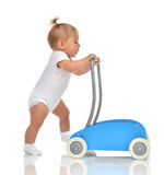 Cute smiling baby girl toddler with toy walker make first steps Royalty Free Stock Images