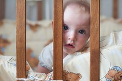 Cute smiling baby looking out of the crib. Funny kid in bed. Close up portrait. Cute smiling baby looking out of the crib. Funny kid in bed Royalty Free Stock Images