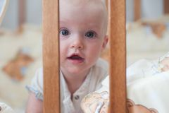 Cute smiling baby looking out of the crib. Funny kid in bed. Close up portrait. Cute smiling baby looking out of the crib. Funny kid in bed Stock Images