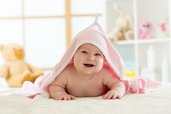 Cute baby lying on belly wrapped with pink towel after bathing royalty free stock photography