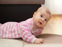 Cute smiling baby lying on floor Royalty Free Stock Photography