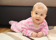 Cute smiling baby lying on floor Royalty Free Stock Image
