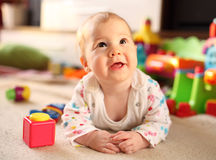 Cute smiling baby lying on floor. Among toys Royalty Free Stock Photo