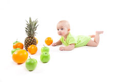 Cute smiling baby lying on his stomach among fruits and looking Royalty Free Stock Photography