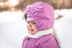 Cute smiling baby portrait in warm clothes in cold sunny winter day Royalty Free Stock Photo