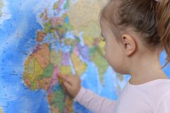 Cute smiling baby searching place on world map stock photography