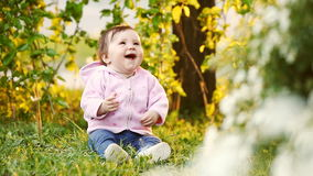 Cute smiling baby seating on the green grass in the park at sunset. stock video