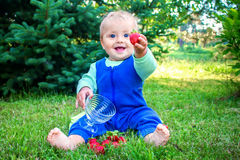Cute smiling baby sitting on a fresh green grass in a park and giving strawberry to the viewer Stock Photo