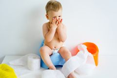 Baby sitting on a potty stock photography
