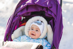 Cute smiling baby sitting in stroller on a cold winter day Stock Photos