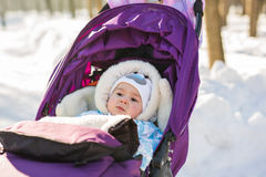 Cute smiling baby sitting in stroller on a cold winter day Royalty Free Stock Images