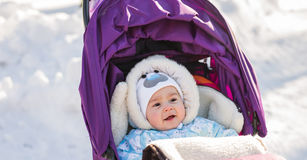Cute smiling baby sitting in stroller on a cold winter day Stock Photography