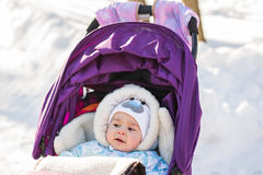 Cute smiling baby sitting in stroller on a cold winter day Stock Photo