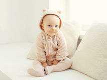 Cute smiling baby sitting in white room home Stock Photos
