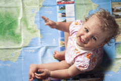 Cute smiling baby sitting on world map and looking at camera with view from above Royalty Free Stock Images