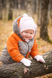 Cute smiling baby stay near fallen tree Royalty Free Stock Photo