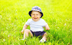 Cute smiling baby wearing a hat sitting on the grass Stock Images