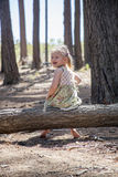 She is cute, smiling blond girl. She is happy to be in forest Stock Photo