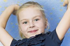 Cute smiling girl with upwards hands. Cute smiling blond girl on blue background with upwards hands royalty free stock photos