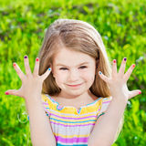 Cute smiling blond little girl with many-coloured manicure royalty free stock image