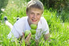 Cute smiling blonde teen boy with pyramid of green. Portrait of cute smiling boy with freckles on his face is holding green apples Stock Photos