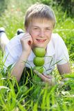 Cute smiling blonde teen boy with pyramid of green. Portrait of cute smiling boy with freckles on his face is holding green apples Royalty Free Stock Photo
