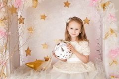 Cute smiling blondy girl with a big Christmas ball Royalty Free Stock Photo