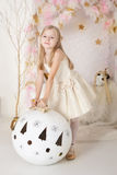 Cute smiling blondy girl with a huge Christmas ball Royalty Free Stock Photography