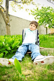 A cute smiling boy. A cute boy sitting on the scateboard on the grass in the yard royalty free stock images