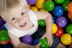 Cute smiling boy. Sitting in colourful balls looking up at camera Royalty Free Stock Image