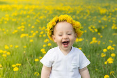 Cute smiling boy in dandelion wreath in the spring field Stock Image