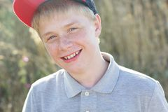 Cute smiling boy with freckles is wearing cap Royalty Free Stock Images