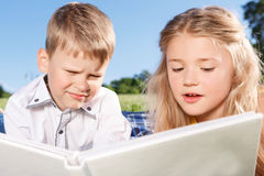 Cute smiling boy and girl reading book Stock Image