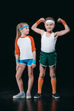 Cute smiling boy and girl in sportswear standing together isolated on black Stock Photos