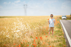 Cute smiling boy hitchhiking along lonely road Royalty Free Stock Photography