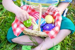 Cute smiling boy holding basket with colorful eggs after easter egg hunt Royalty Free Stock Photography